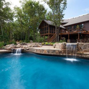 Diseño de piscinas y jacuzzis de estilo americano, grandes, a medida, en patio trasero, con losas de hormigón