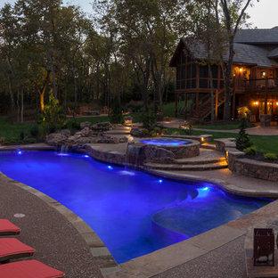 Modelo de piscinas y jacuzzis de estilo americano, grandes, a medida, en patio trasero, con losas de hormigón
