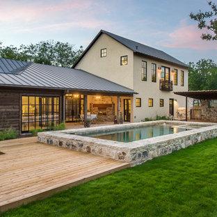 Esempio di una piscina country rettangolare dietro casa con pedane