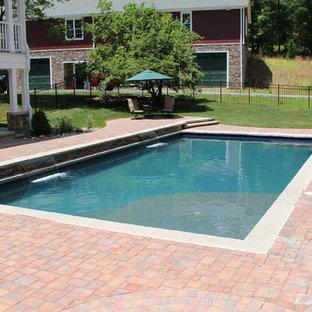 Foto de piscina con fuente natural, de estilo americano, grande, rectangular, en patio trasero, con adoquines de ladrillo