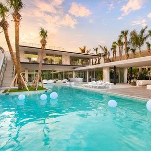 Foto di una piscina stile marino personalizzata dietro casa con un acquascivolo e pedane