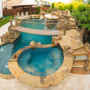 Idee per una grande piscina tropicale personalizzata dietro casa con un acquascivolo e pavimentazioni in pietra naturale