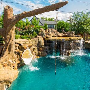 Idéer för en stor exotisk pool på baksidan av huset, med vattenrutschkana och naturstensplattor