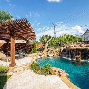 Ejemplo de piscina con tobogán tropical, grande, a medida, en patio trasero, con adoquines de piedra natural