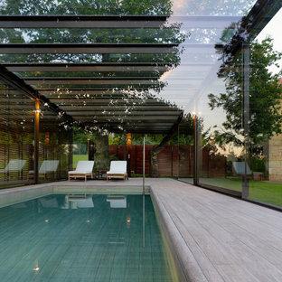 Foto de casa de la piscina y piscina contemporánea, grande, rectangular y interior, con entablado
