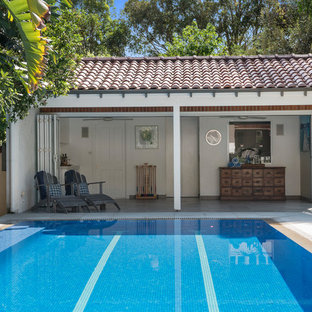 Inspiration for an expansive traditional backyard rectangular infinity pool in Sydney with a pool house and natural stone pavers.