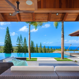 Photo of a large tropical backyard rectangular infinity pool in Hawaii with a hot tub and concrete slab.
