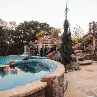 Esempio di una grande piscina stile americano personalizzata dietro casa con fontane