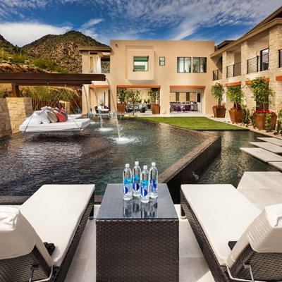 Inspiration for a huge southwestern backyard stone and custom-shaped infinity pool fountain remodel in Phoenix