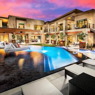 Ejemplo de piscina con fuente infinita, de estilo americano, extra grande, a medida, en patio trasero, con adoquines de hormigón
