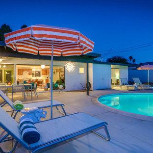 Foto de piscina natural, retro, de tamaño medio, redondeada, en patio trasero, con adoquines de hormigón