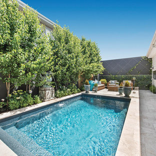 This is an example of a small traditional courtyard rectangular lap pool in Melbourne with a water feature and natural stone pavers.
