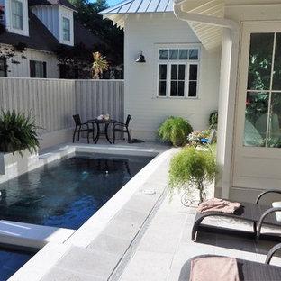 Modelo de piscinas y jacuzzis tradicionales, pequeños, en forma de L, en patio trasero, con suelo de baldosas