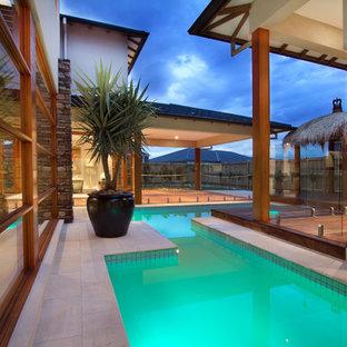 メルボルンのオーダーメイドトロピカルスタイルのおしゃれな中庭プールの写真