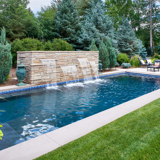 Large contemporary backyard rectangular lap pool in Denver with a water feature.