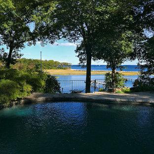 Foto de piscina natural, de estilo americano, grande, a medida, en patio trasero, con adoquines de hormigón