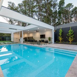 Modelo de piscina moderna, pequeña, rectangular, en patio, con adoquines de hormigón