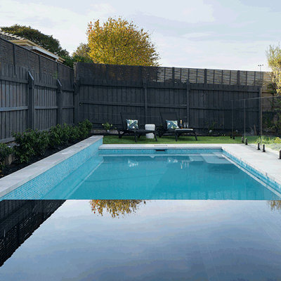 Example of a large minimalist backyard concrete paver and rectangular lap hot tub design in Melbourne