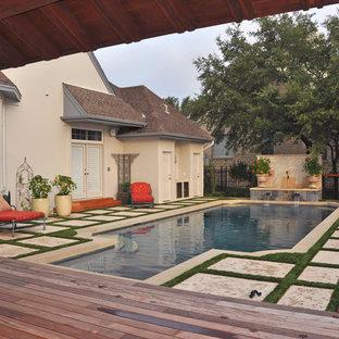 Modelo de piscina con fuente elevada, clásica, grande, rectangular, en patio trasero, con adoquines de hormigón
