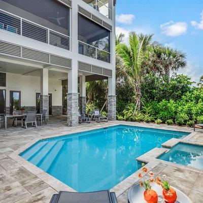 Island style backyard custom-shaped hot tub photo in Miami