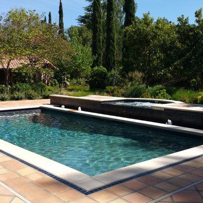 Pool fountain - mid-sized mediterranean backyard tile and rectangular lap pool fountain idea in San Francisco