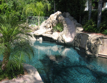Pool and patio with stone / rock walls and deck