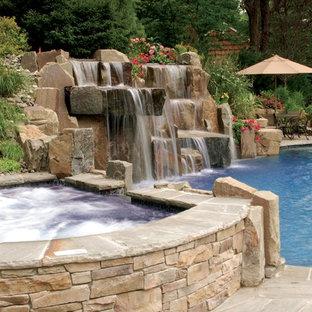 Exemple d'une grande piscine arrière chic sur mesure avec un bain bouillonnant et des pavés en pierre naturelle.