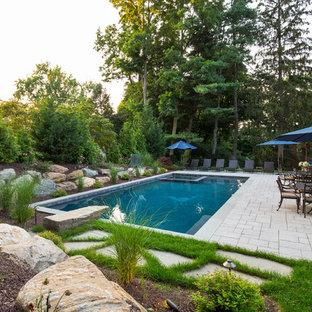 Immagine di una grande piscina monocorsia classica rettangolare dietro casa con una vasca idromassaggio e pavimentazioni in pietra naturale