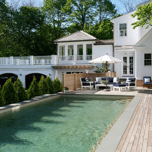 Pool house - large traditional backyard rectangular lap pool house idea in Boston with decking