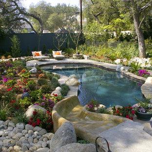 Exemple d'une grand piscine arrière chic sur mesure avec des pavés en pierre naturelle et un toboggan.