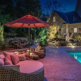 Diseño de piscina con fuente natural, tradicional, grande, rectangular, en patio trasero, con suelo de hormigón estampado