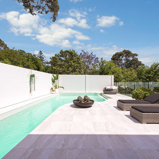 This is an example of a modern backyard custom-shaped lap pool in Sydney with tile.