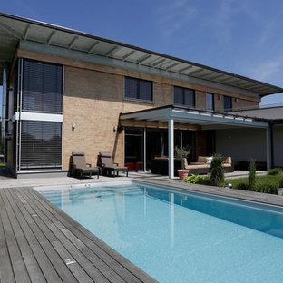 Großer Mediterraner Pool hinter dem Haus in rechteckiger Form mit Dielen in Sonstige