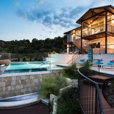 Large tuscan backyard tile and rectangular aboveground hot tub photo in Austin