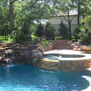 """Foto di una grande piscina monocorsia tradizionale a """"C"""" dietro casa con fontane e pavimentazioni in cemento"""