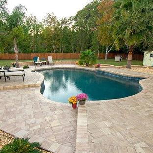 Foto de piscina infinita, clásica, de tamaño medio, a medida, en patio trasero, con adoquines de piedra natural
