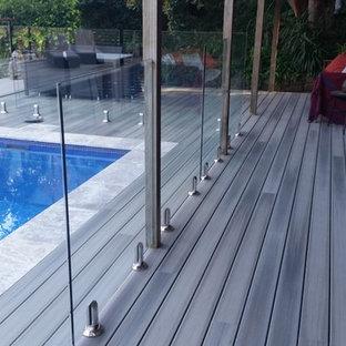 Ejemplo de piscina elevada, actual, grande, rectangular, en patio trasero, con entablado