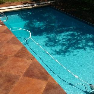 Ejemplo de piscina de tamaño medio, redondeada, en patio trasero, con losas de hormigón