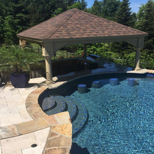Large country backyard custom-shaped pool in Philadelphia with natural stone pavers and a pool house.