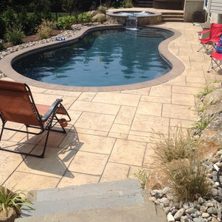 Example of a large island style backyard stone and custom-shaped natural hot tub design in Philadelphia