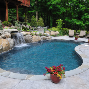 Design ideas for a large country backyard custom-shaped natural pool in Philadelphia with a hot tub and natural stone pavers.