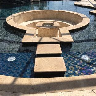 Immagine di una grande piscina naturale classica rotonda con pavimentazioni in pietra naturale