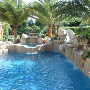 This is an example of a large tropical backyard custom-shaped natural pool in Tampa with a water slide and brick pavers.