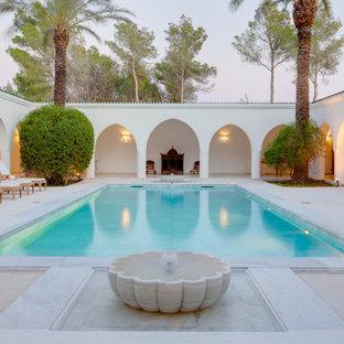 Foto de piscina con fuente mediterránea, grande, rectangular, en patio, con adoquines de piedra natural