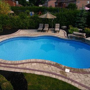 Imagen de piscina alargada, tradicional renovada, de tamaño medio, a medida, en patio trasero, con adoquines de hormigón
