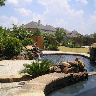 Idées déco pour une grand piscine naturelle et arrière craftsman sur mesure avec un bain bouillonnant et une dalle de béton.