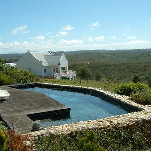 Foto de piscina elevada, tradicional, en forma de L, en patio delantero, con entablado