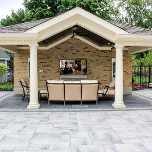 Imagen de casa de la piscina y piscina tradicional, grande, rectangular, en patio trasero, con adoquines de hormigón