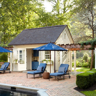 Inspiration for a traditional pool in New York with brick pavers and a pool house.