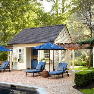 Immagine di una piscina chic con pavimentazioni in mattoni e una dépendance a bordo piscina